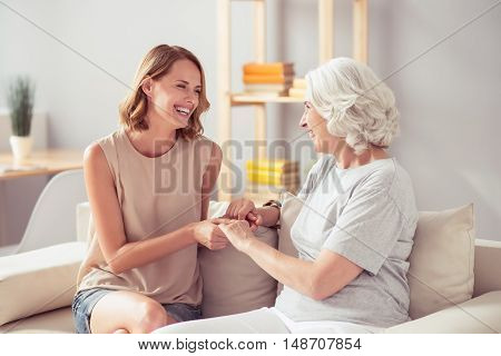 Full of gladness. Cheerful delighted young woman sitting on the couch and holding hands of her grandmother while resting together