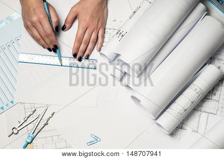 Architect working on blueprint. Architects workplace - architectural project blueprints ruler and divider compass. Construction concept. Engineering tools. Top view