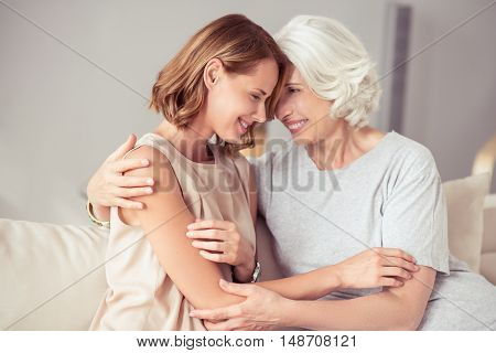 My dear. Positive delighted age woman sitting on the couch and embracing with her daughter while expressing joy at home