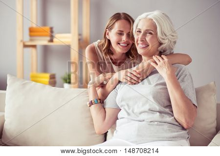 Love you so much. Positive beautiful adult woman embracing her mother who is sitting on the couch while resting at home together