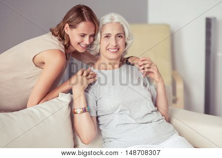 Happy moments. Delighted positive aged woman sitting on the couch and expressing gladness while embracing with her daughter