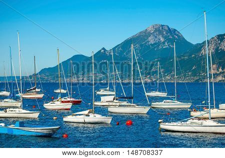 White sailing vessel yachts on Garda lake. Veneto region. Italy. Landscape of marine regatta with floating boats in the harbor high Alpine mountains background