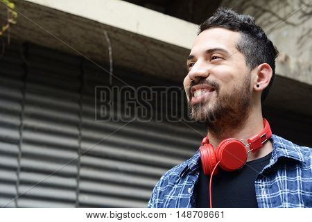 Portrait of young latin man with red headphones. Urban scene.