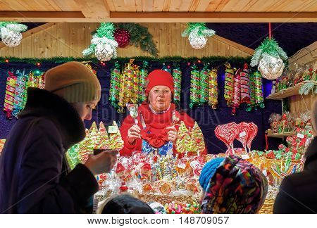 Seller At Stall With Colorful Candies At Vilnius Christmas Market