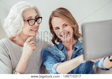 Leave it in memory. Joyful delighted senior woman and her adult daughter using tablet and making selfies while having fun at home