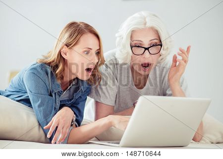 In astonishment. Pleasant surprised adult woman and her mother resting on the couch and using laptop while expressing wonder