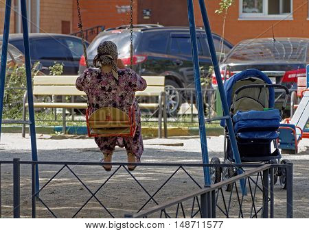 Woman in the Central Asian clothes swinging on the swing at the playground next to a pram