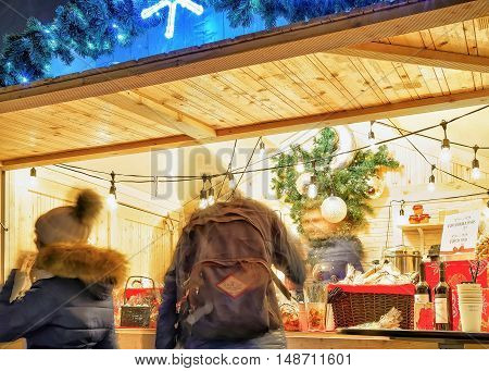 Vilnius Lithuania - December 272015: People looking for festive goods and souvenirs at Christmas Market. Motion blur. Selective focus.