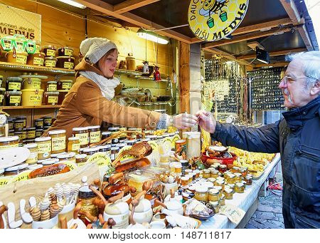 Riga Latvia - December 25 2015: Woman is selling homemade honey and ceramics at the Riga Christmas Market. The fair is an annual part of celebrations and takes place in December. Selective focus