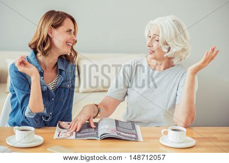 Daily press. Cheerful delighted adult woman and her mother sitting at the table and reading magazine while having a pleasant conversation