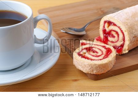 Sweet Roll With Jam And Tea Spoon On A Cutting Board. Cup Of Tea On A Wooden Table.