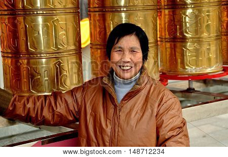 Pengzhou China - November 26 2013: Smiling Chinese woman standing next to a row of metal Tibetan prayer wheel drums at the Long Xing Temple