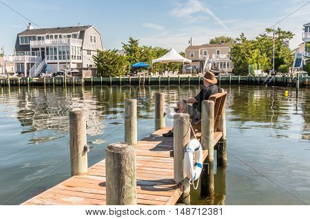 Man seated on bench on the dock looking out into Little Egg Harbor Long Beach Island New Jersey.