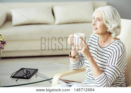 Pleasant days. Nice relaxed aged woman sitting at the table and looking aside while drinking tea at home