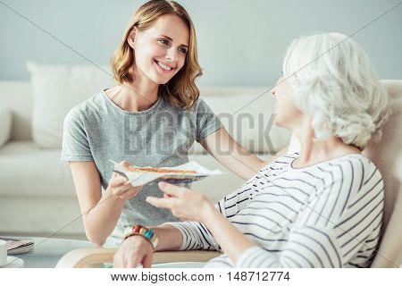 My favorite dish. Delighted pleasant woman sitting in the chair while her adult daughter bringing her a plate with tasty pie