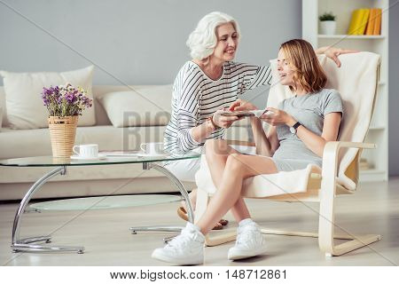 For you. Cheerful loving aged woman holding plate with pie and giving it to her adult smiling daughter while resting at home