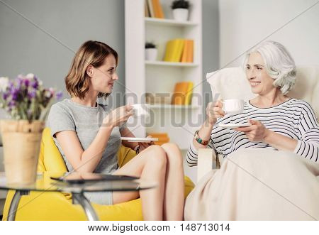 Lets make a tea party. Positive content woman and her smiling grandmother sitting and drinking tea while having rest at home