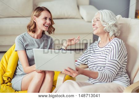 Full of emotions. Delighted joyful beautiful woman and her grandmother smiling and using laptop while having a pleasant conversation