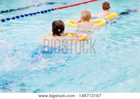 Seven Years Old Boy Learning To Swim At The Pool.