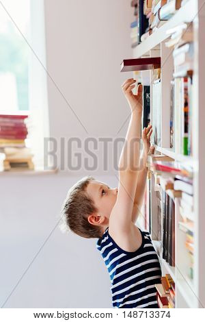 Seven Years Old Boy Reaching For Book In Library.