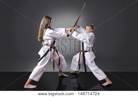 Male and female young karate fighting with swords on the gray background