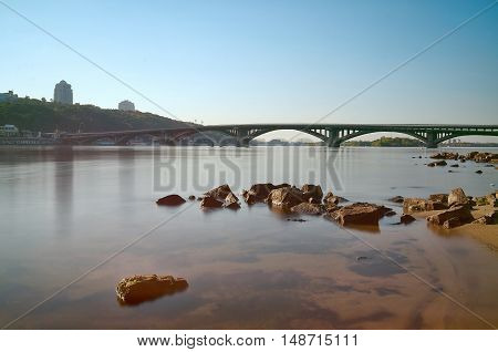 Railway bridge across the blue Dnieper river in summer in Kiev,Ukraine.Beautiful View of Dnipro river, tower buildings, embankment,river stones,subway bridge,shore,blue sky. Cityscape