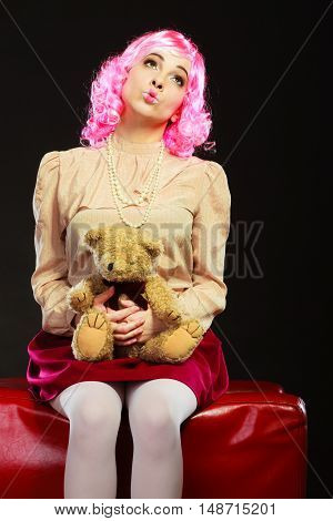 Mental disorder concept. Young childlike woman wearing like puppet doll sitting with teddy bear toy on red couch dark black background
