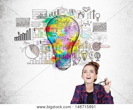Nerd girl is sitting near concrete wall with startup sketch and large colorful light bulb. Concept of young startup employee
