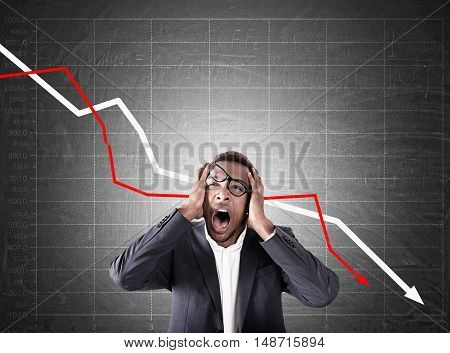 Portrait of frustrated African American businessman standing near chalkboard with white and red graphs going down. Concept of failure in business and bad analysis.