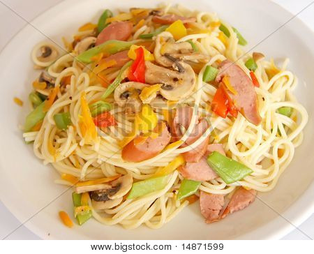 Fried noodle pasta fusion cuisine with sausages and vegetables