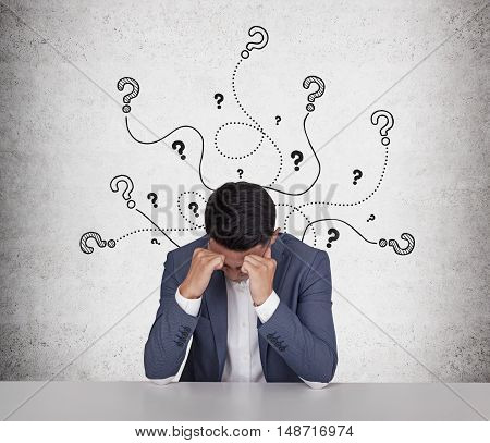 Stressed out Asian businessman sitting near concrete wall with question mark sketches on it. Concept of too many questions