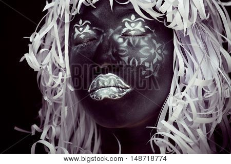 creative makeup like Ethiopian mask, white pattern on black face close up, halloween horror, fashion style print