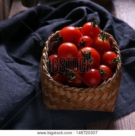 Dark and moody tomatoes in a basket.