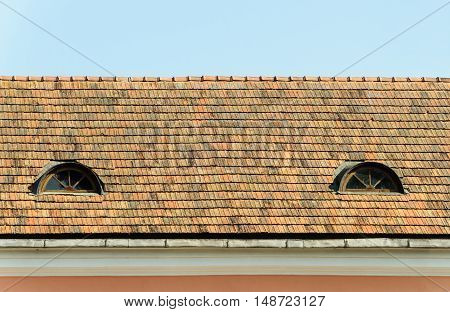 Old tiled roof with two attic windows in the Trinity suburb old part of Minsk Belarus