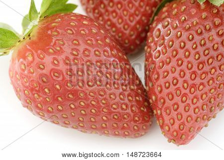 Three delicious red strawberries on white table as seen from a close up view