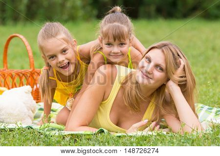 Mother And Two Daughters Lie On Each Other On The Green Grass