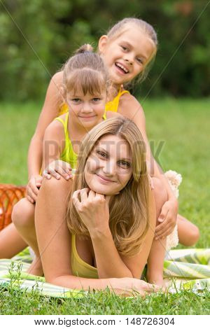 Two Daughters Are Sitting On The Young Mother, Who Is Lying On The Green Grass