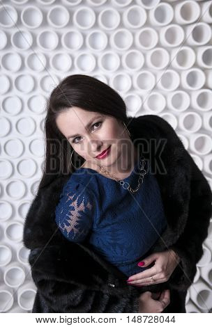 Girl in black fur coat on the decorative background