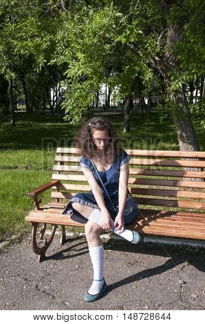 The girl in the blue dress dress shoes on a wooden bench in the park