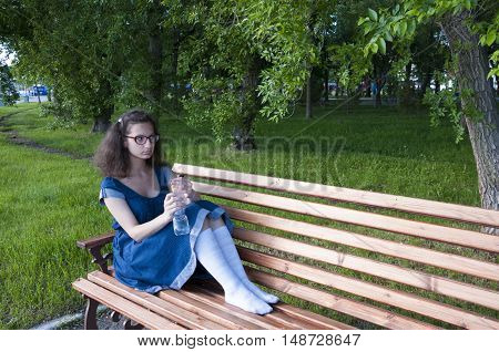 A girl sits on a park bench with a bottle of water
