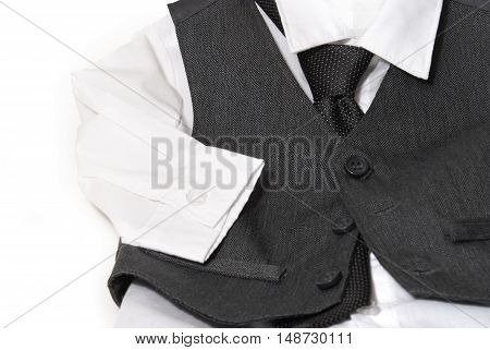 An infants dress shirt and vest are laid out for the parents to clothe their child before the formal day of events.