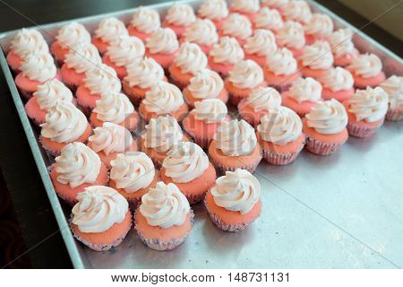 The process of decorating cupcakes on tray