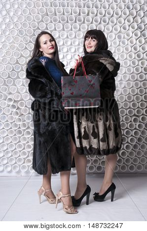 Women in fur coats with their purchases in full growth