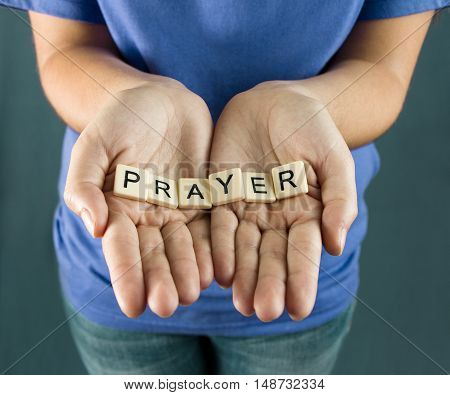 Prayer Spelled in Tiles in a young girls hands