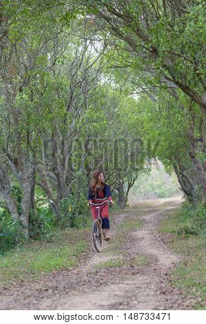 Young asian women rideing an old bike in field.Thailand