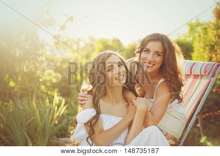 Two sisters. Girls embracing in the garden. Family time. Human relationships. Portrait.