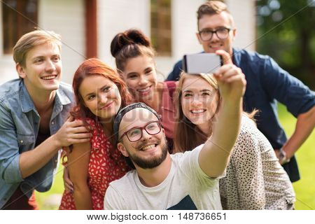 leisure, holidays, reunion, people and friendship concept - happy teenage friends taking selfie by smartphone at summer house
