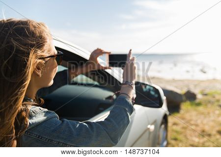 summer vacation, holidays, travel, road trip and people concept - happy teenage girl or young woman in car taking picture of sea with smartphone