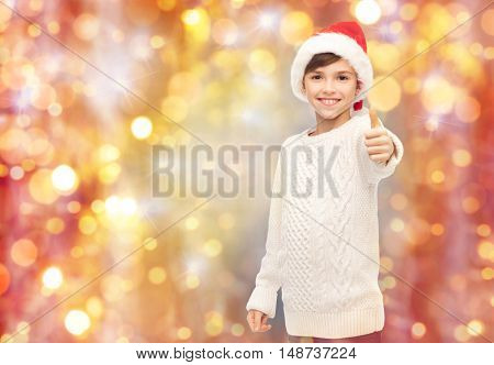 holidays, gesture, christmas, childhood and people concept - smiling happy boy in santa hat showing thumbs up over lights background