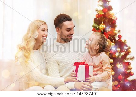 family, christmas, holidays and people concept - happy mother, father and little daughter with gift box sitting on sofa at home over lights
